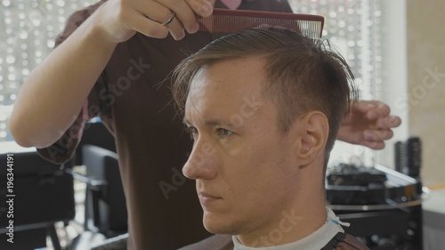 Plexiglas Kapsalon Close-up of hairdresser combs male client by hand after haircut.