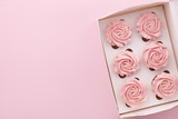 Muffins or cupcakes with flower shaped cream in box on pink background, top view - 196345564
