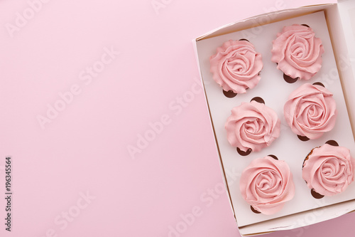 Wall mural Muffins or cupcakes with flower shaped cream in box on pink background, top view
