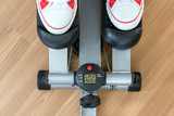 Exercise on a stepping machine, looking from above. Active person with sport shoes exercising on stepper on wooden floor, close up. - 196357312