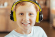 Favourite hobby. Portrait of a positive cute delighted boy smiling and looking at you while wearing headphones