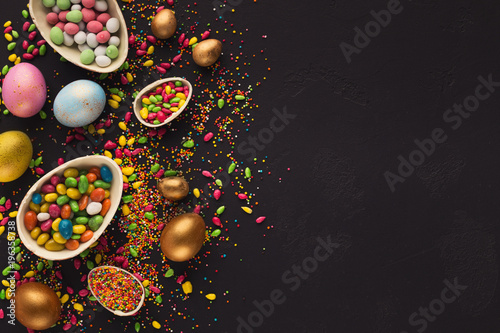 Poster Colorful easter eggs and sprinkles on black background
