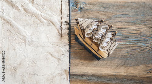 Keuken foto achterwand Schip old paper, rope and model classic boat on wood background