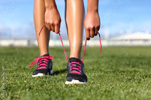 Running and fitness exercise sport girl getting ready tying shoes jogging on park grass. Summer active lifestyle. - 196367140