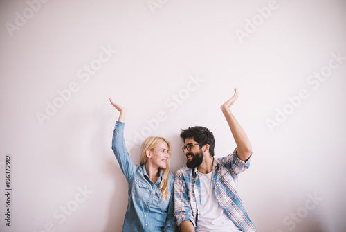 Happy charming young love couple looking each other and with raised arms holding the empty space above while sitting on the floor.