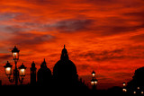 Red blood sky sunset over Venice Lagoon with Salute Basilica domes and old lamps