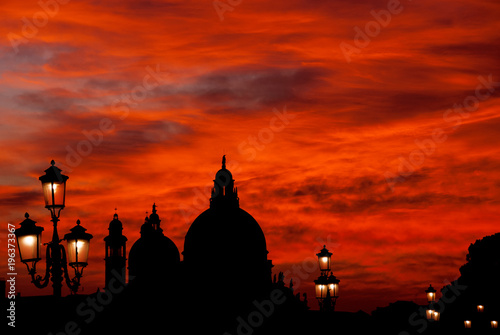 Foto op Canvas Venetie Red blood sky sunset over Venice Lagoon with Salute Basilica domes and old lamps