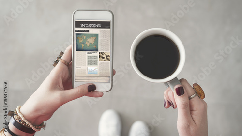 Woman holding mobile phone and reading news from screen other hand holding coffee cup