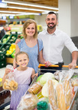 Portrait of  family standing with full cart in supermarket - 196379122