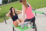Woman doing sit ups using park equipment - 196379134