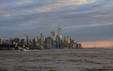 New York downtown panorama at sunset with cloudy sky and Hudson river in the foreground