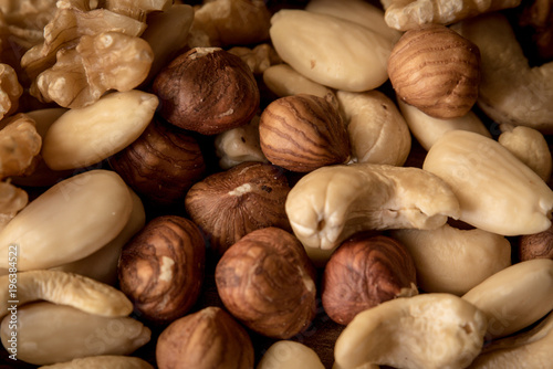 Wall mural nuts, in a white bowl, fried on a dark wood background, mixture of walnuts, almonds and roasted nuts, top view