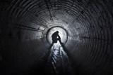 Men seating in underground tunnel