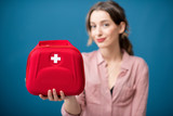 Portrait of a woman with first aid kit on the blue wall background - 196395935