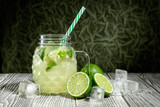 Lemonade in a glass jar with slice of lime and ice cubes