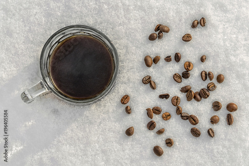 Papiers peints Café en grains A mug of black coffee stands in the snow, scattered beans