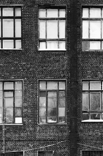 Facade of an old brick building in loft style. High Windows and textural materials. Black and white styling - 196408976