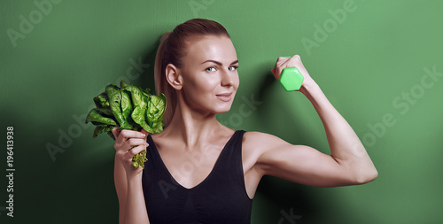 girl in sports top holds gattelu and bunches of spinach