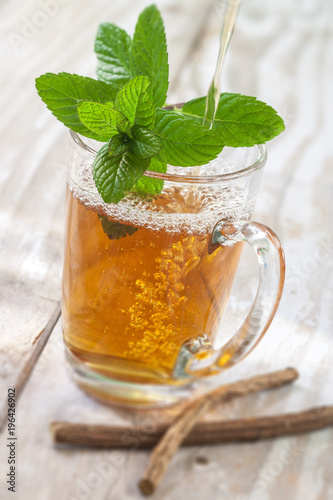 Arabic nana mint tea in traditional glass with mint, cinnamon, on a old white wooden board