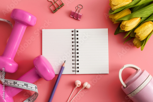 Styled stock photography of fitness equipment dumbbells notepad pencil and earphone on pink background. Flat lay.