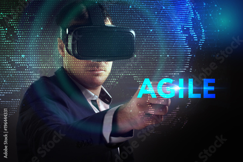 Business, Technology, Internet and network concept. Young businessman working in virtual reality glasses sees the inscription: Agile