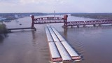 A beautiful aerial of a barge traveling under a steel drawbridge on the Mississippi River. - 196447306