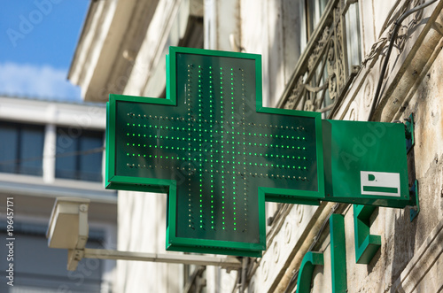Deurstickers Apotheek Closeup of a green pharmacy sign outside a pharmacy store in France.