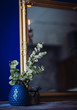 Little blue vase with green branches stands before a mirror on a table