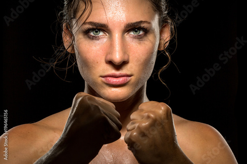 Female empowering inspiring motivational portrait of female fighter in self defense stance