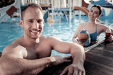 Time to relax. Muscular young man standing in a swimming pool and looking into the camera with a cheerful smile on his face while enjoying his summer holidays. - 196465712