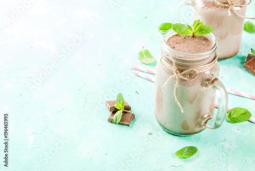 Foto op Plexiglas Milkshake Chocolate smoothie or milkshake with mint and straw, in mason jar on light blue background, copy space