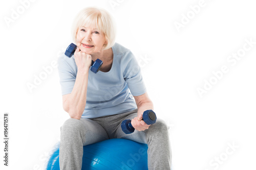 Wall mural Senior sportswoman sitting on fitness ball with dumbbells in hands isolated on white