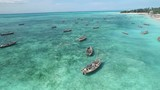 Rustic wooden boats for fishing sitting in calm waters of Zanzibar, Tanzania, aerial - 196477102