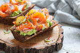Smorrebrod with salmon on rye bread with vegetables and herbs