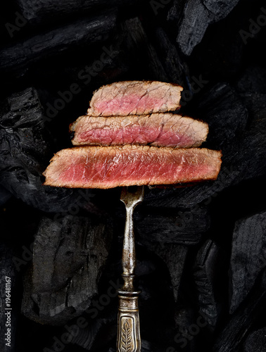 Fotobehang Steakhouse Slices of Medium rare grilled Steak Ribeye on meat fork on black background