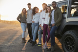 Young adult friends on a road trip standing by their jeep - 196486585