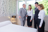 hotel service housekeeping workers and manager in a hotel room - 196487305