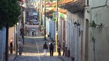 A beautiful shot of the buildings and cobblestone streets of Trinidad, Cuba with pedestrians. - 196487997