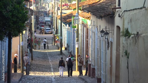 A beautiful shot of the buildings and cobblestone streets of Trinidad, Cuba with pedestrians.