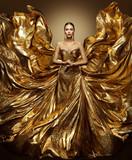 Gold Woman Flying Dress, Fashion Model in Waving Golden Gown, Fluttering Fabric Fly like Wings, Art Beauty Portrait - 196490943