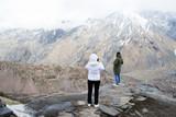 Туристы смотрят на горы Грузии. Высоко в горах  - 196492135