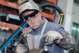 Senior worker using gas torch
