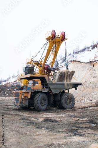 Aluminium Trekker Excavator loads dump truck in quarry in winter
