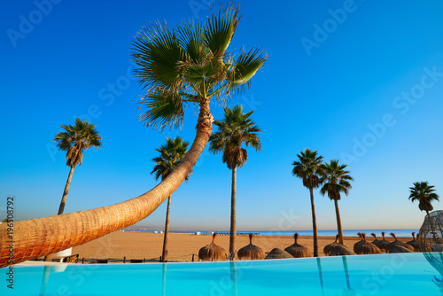 Resort infinity pool in a beach with palm trees