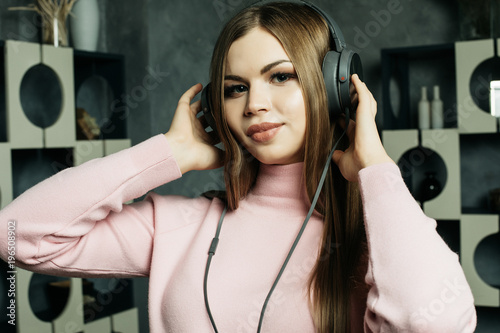 Fototapeta people and technology concept - happy woman in headphones listening to music from smartphone