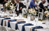 Table set up for wedding reception with people out of focus in background. - 196512199