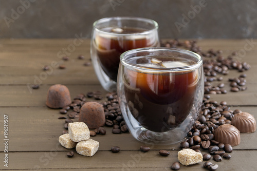 Papiers peints Café en grains Coffee in double-walled glass on a wooden table.