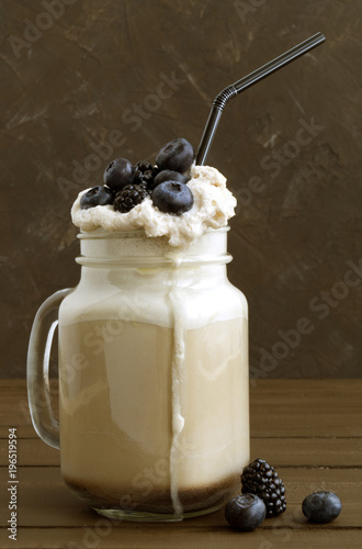 Poster Coffee milk shake with fresh berries on wooden background.