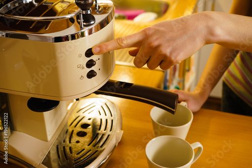 Poster Woman making hot drink in coffee machine