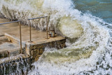 Waves come crashing on the pier during a major storm - 196537917